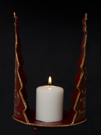 Close-up image of a red vintage candle holder with lighted candle on a dark background