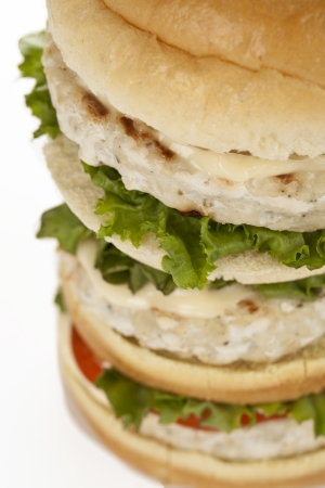 Cropped image of tall hamburger with meat and vegetables over the white background photo