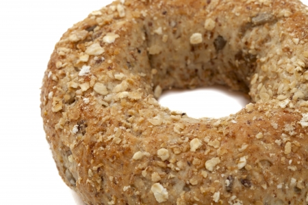 A single whole grain wheat bagel on a white background Stock Photo - 17167533