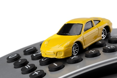 Close up image of yellow toy car on calculator against white background Stock Photo - 17152435