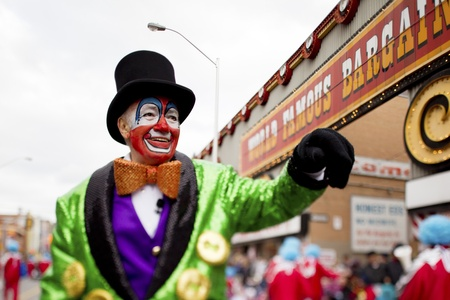 Close-up view of a smiling man in clowns costume with hand raised at Christmas parade.