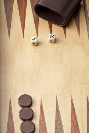 Close-up shot of wooden backgammon board with dices and brown pieces with cup. photo