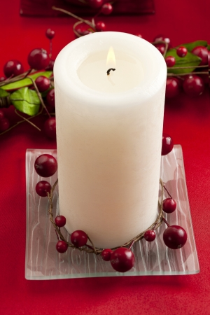 Close-up shot of burning candle stick with fake red berry fruits. photo