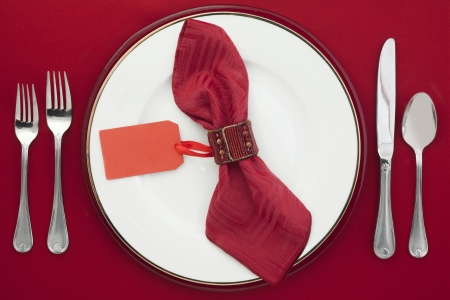 Dining Etiquette with silverware, ceramic plate and place card on a napkin photo