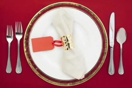 banqueting: Horizontal image of dinner table with utensils and empty tag on a red background