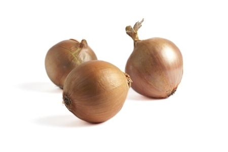 Close up image of three fresh golden onions against white background