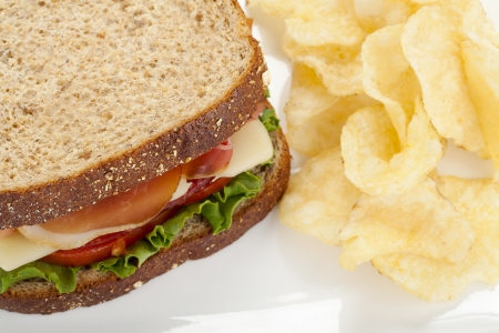 Close up image of ham sandwich with potato chips against white background photo