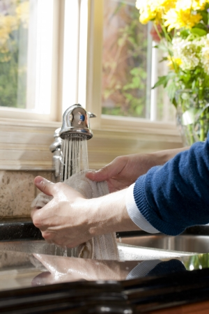 Human hand washing a rag in the faucet Stock Photo - 17152970