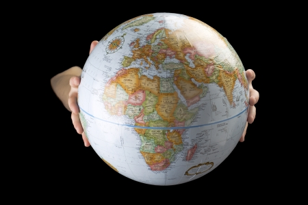 lifting globe: Close up image of human hand holding earth globe against black background Stock Photo