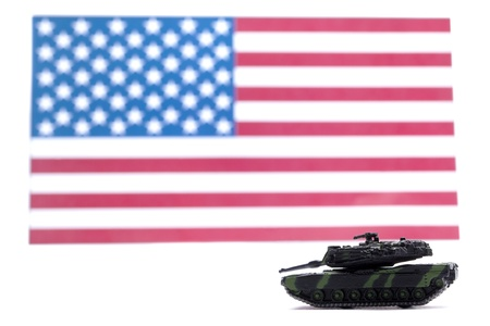 Image of a toy military tank guarding the American flag isolated on a white background