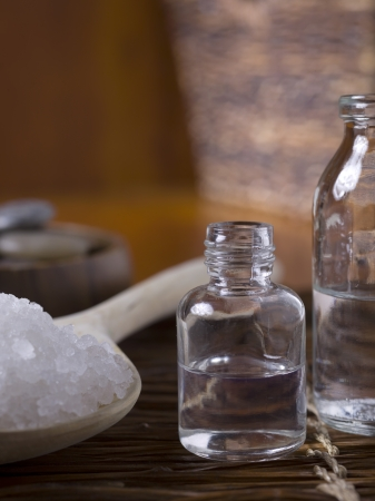 Cropped image of an oil spa with salt and blurred bowl of stones on the background Stock Photo - 17152646