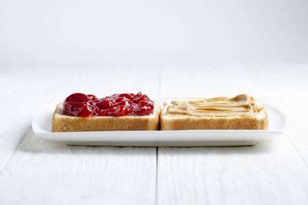 smeared: Peanut butter and strawberry jam sandwich on a white plate