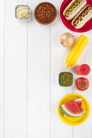 Hotdog sandwiches, watermelon slices  and condiments arranged in a table Stock Photo - 17155417