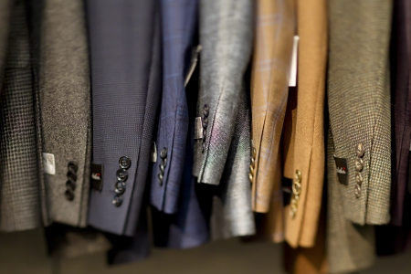 sleeve: Close-up of suits hanging in store.