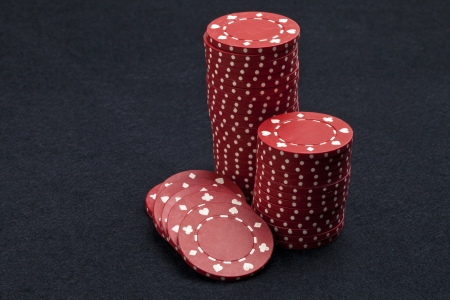 Red poker chips over a dark background