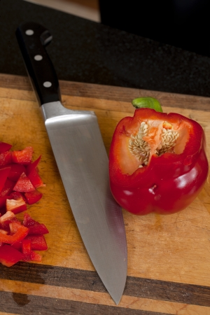 Close up image of red bell pepper with a kitchen knife
