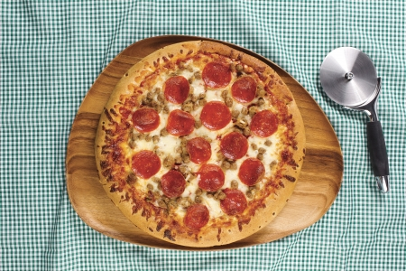 Close-up overhead shot of pepperoni pizza in wooden plate with pizza cutter on table cloth. Stock Photo - 17170912