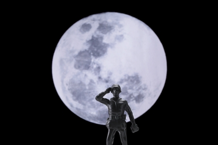 plastic soldier: Saluting soldier under the full moon Stock Photo