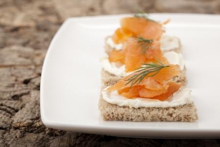 Smoked salmon, cream cheese and dill crackers in a white plate Archivio Fotografico