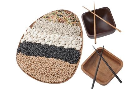 bol vide: Coup de t�te de la plaque en bois avec des haricots et un assortiment de bol vide avec des baguettes Banque d'images