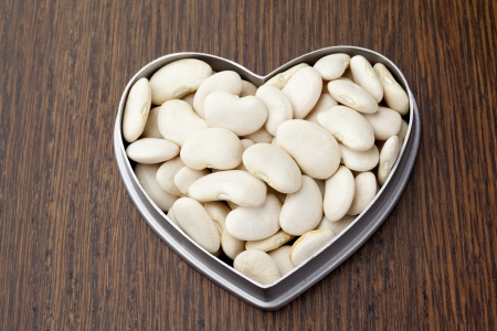 Close-up shot of white kedney beans in heart shape container on wooden table. Stock Photo - 17168663