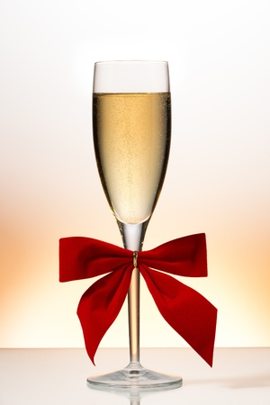 celebration champagne: Champagne flute with red ribbon bow Stock Photo