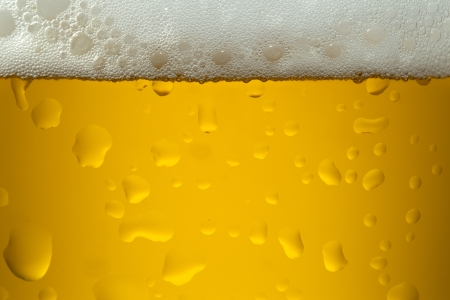 A close-up image of a yellow color beer into the glass photo