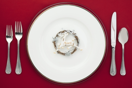 Close-up overhead shot of plate with plastic deer and silverware on red table cloth. Stock Photo