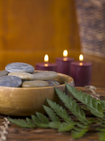 lighted: Cropped image of a wooden bowl with spa stones and lighted candle on the background Stock Photo