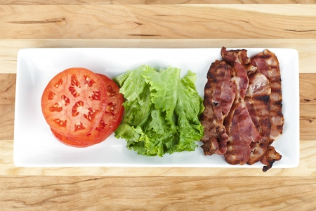 Plate of tomato, lettuce and crispy bacon over a wooden background photo