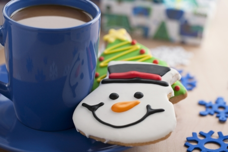 A plate of a blue mug with coffee and a smiling snowman cookie on the side photo