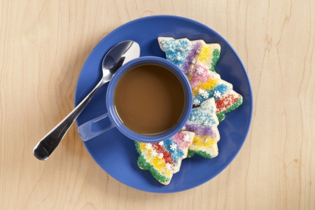 A blue plate on the table with a mug of coffee and a cookie with a spoon on the side photo