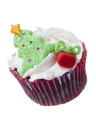 A vertical image of a chocolate cupcake with a Christmas tree and gift box decoration on top Imagens