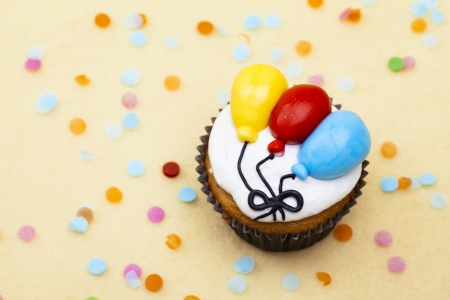 Close-up top view of a cupcake with colorful balloon design. Imagens