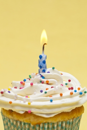 Close-up shot of a cupcake with sugar icing with burning candles over yellow background.