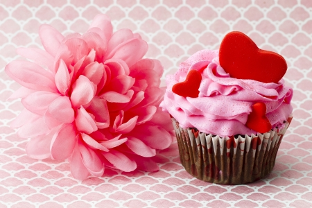 Close-up image of strawberry cupcake with heart shapes on it and a pink flower beside it. photo