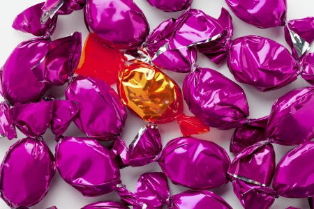 Close-up shot of a shiny purple candies surrounding a golden shiny hard candy. photo