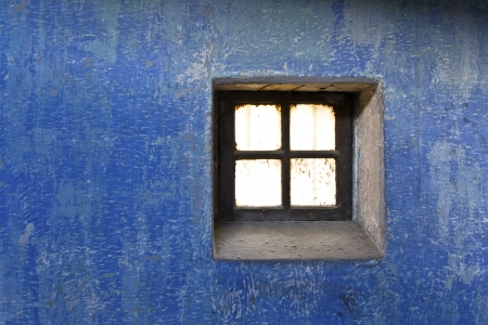 run down: Close-up image of a old blue wall with rusty window.