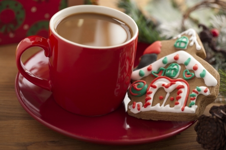 Close-up image red coffee mug with gingerbread house in saucer. photo