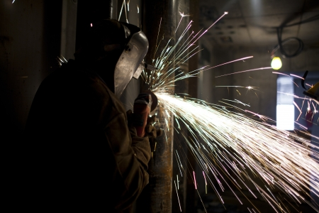 View of a welder cutting metal in protective workwear. Stock Photo
