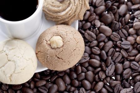 Imagen de la infusión de café y galletas surtidas en un plato blanco con granos de café Foto de archivo - 17208273