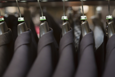 Close-up of business suits hanging in clothing store. photo
