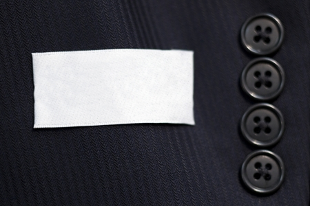 sleeve: Close-up of buttons on sleeve of mans black suit.