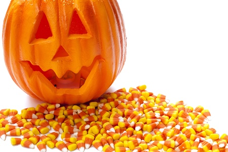 rubbery: Pumpkin with a carved smiling face on top of candy corn pile.