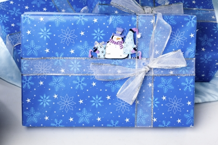 Blue Christmas box wrapped with shiny ribbon with snowman sticker. photo