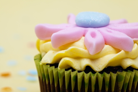 Detailed shot of a colorful cupcake with pink floral pattern.