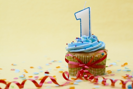 first birthday: Close-up shot of a cupcake with number 1 candle and red streamer tied around it. Stock Photo
