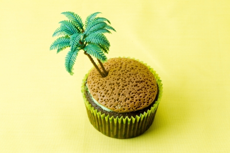 Close-up image of cupcake with plastic coconut tree miniature over plain yellow background.