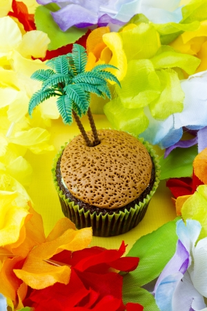 High angle close-up shot of cupcake with plastic coconut tree miniature surrounded by colorful flowers. Imagens