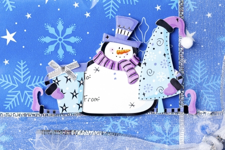 Extreme close-up image of snowman sticker on blue Christmas box. photo